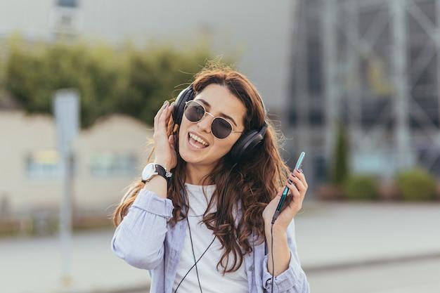 Giovane studentessa graziosa in attesa di un taxi e ascolto di musica