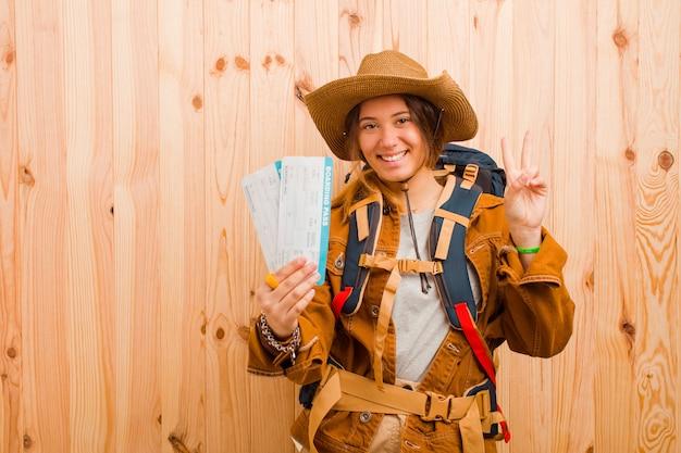 Giovane donna graziosa del viaggiatore con i biglietti di una carta d'imbarco