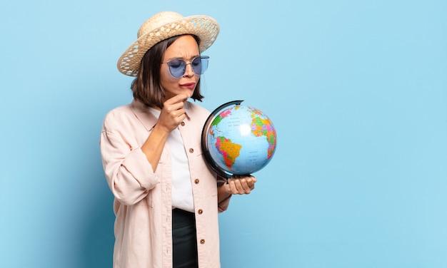 Giovane donna graziosa del viaggiatore con una mappa del globo del mondo. concetto di viaggio o vacanze