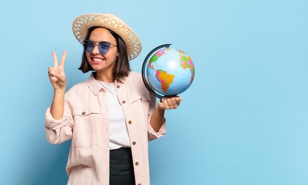 Giovane donna graziosa viaggiatore con una mappa del globo del mondo. concetto di viaggio o vacanze