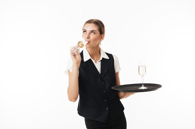 Giovane cameriera graziosa in uniforme che tiene vassoio con vetro sognante
