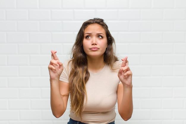 Giovane donna graziosa contro il muro bianco