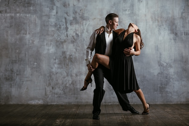 La giovane donna graziosa in vestito nero e l'uomo ballano il tango