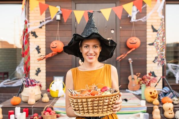 Giovane donna graziosa in cappello nero della strega di halloween che tiene il cestino con i dolci mentre aspetta i bambini di halloween contro la porta decorata