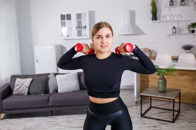 Giovane bella donna in un top nero con manubri in mano che fa sport a casa, fitness a casa durante la quarantena. uno stile di vita sano