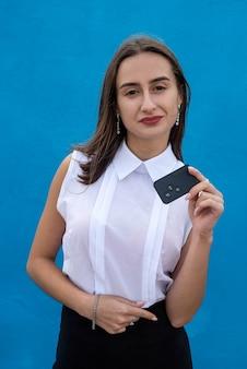 La giovane donna graziosa in panno di affari tiene la chiave dell'automobile su fondo blu