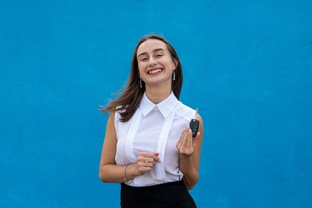La giovane donna graziosa nel panno di affari tiene la chiave dell'automobile su priorità bassa blu