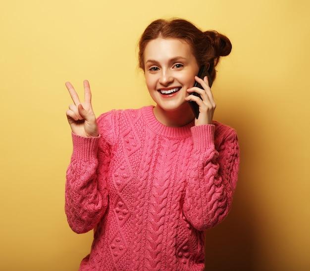 Giovane donna graziosa che chiama dal telefono