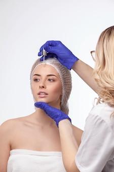 Una giovane donna graziosa è venuta in un salone di bellezza e si consulta con un'estetista sui trattamenti antietà