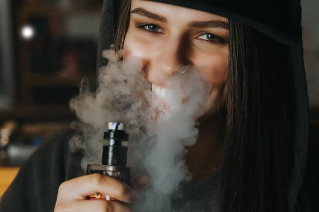 La giovane donna graziosa in cappuccio fuma una sigaretta elettronica al negozio del vape. stile hip-hop. avvicinamento.