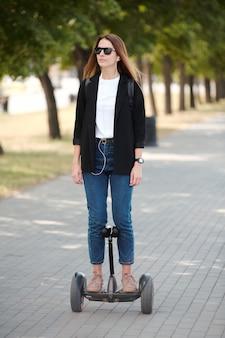 Giovane donna graziosa in abbigliamento casual e occhiali da sole in piedi su uno scooter elettrico mentre si muove lungo la strada nel parco pubblico il giorno d'estate