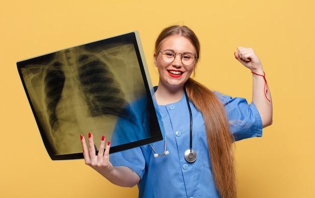 Giovane bella donna che celebra un trionfo come un'infermiera vincitrice concept