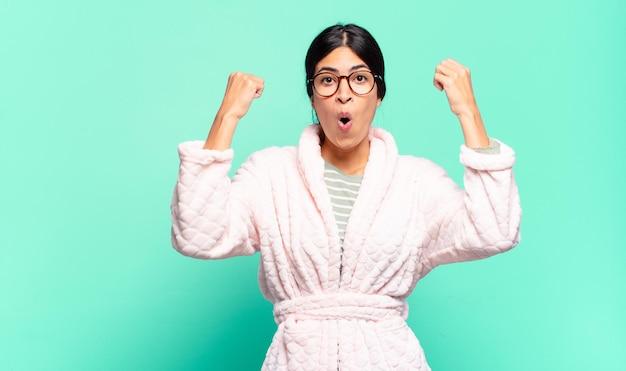 Giovane bella donna che celebra un incredibile successo come una vincitrice, con un'aria entusiasta e felice di dire prendilo!. concetto di pigiama
