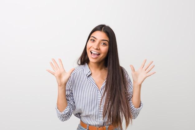 Giovane bella donna che celebra una vittoria o un successo, è sorpreso e scioccato