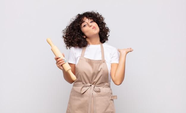 Chef giovane donna graziosa che si sente perplesso e confuso, dubbioso, ponderato o scegliendo diverse opzioni con un'espressione divertente