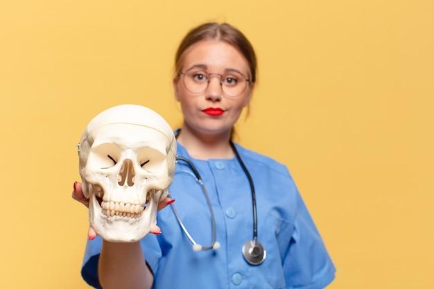Concetto dell'infermiera di espressione confusa della giovane donna graziosa