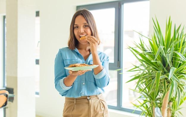 Giovane donna graziosa che cucina a casa