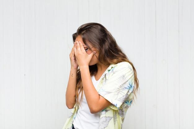 Giovane donna graziosa che copre gli occhi con le mani con uno sguardo triste e frustrato di disperazione, pianto, vista laterale