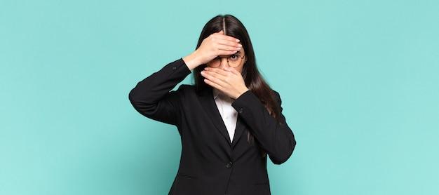 Giovane donna graziosa che copre il viso con entrambe le mani dicendo no alla fotocamera! rifiutare le immagini o vietare le foto. concetto di affari