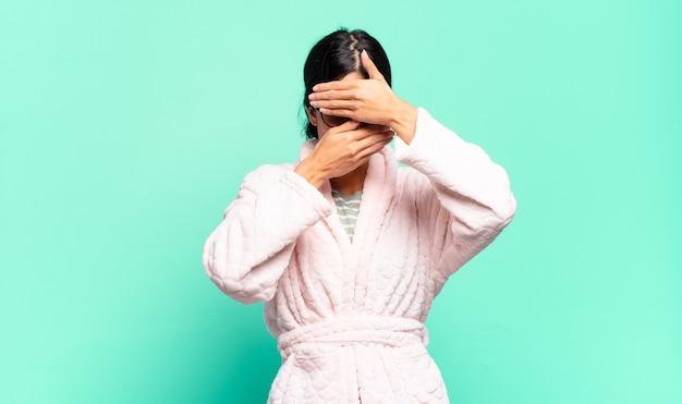 Giovane donna graziosa che copre il viso con entrambe le mani dicendo no alla fotocamera! rifiutare le immagini o vietare le foto. concetto di pigiama