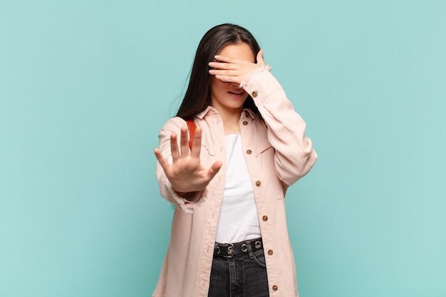 Giovane bella donna che copre il viso con la mano e mette l'altra mano davanti per fermarsi, rifiutando foto o immagini. concetto di studente