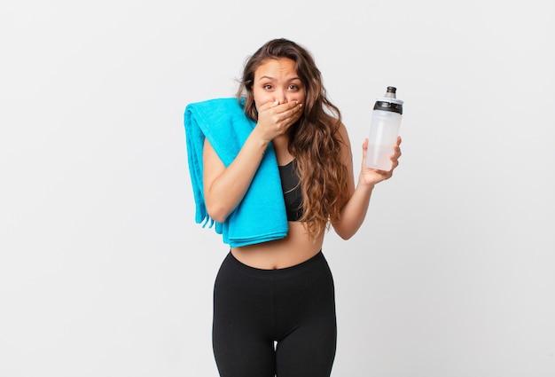Giovane donna graziosa che copre la bocca con le mani con uno scioccato. concetto di fitness