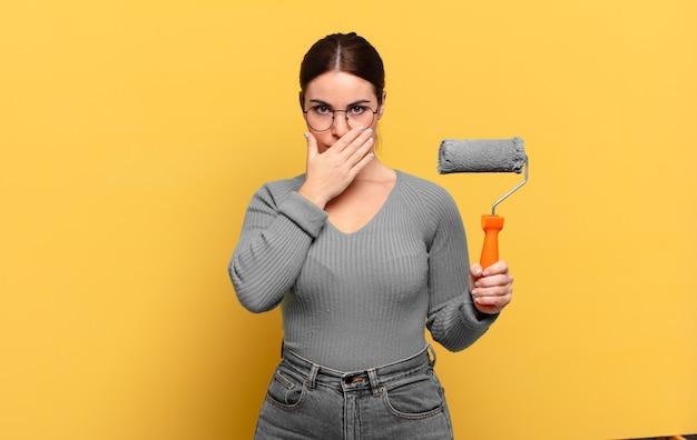 Giovane donna graziosa che copre la bocca con le mani con un'espressione scioccata e sorpresa, mantenendo un segreto o dicendo oops
