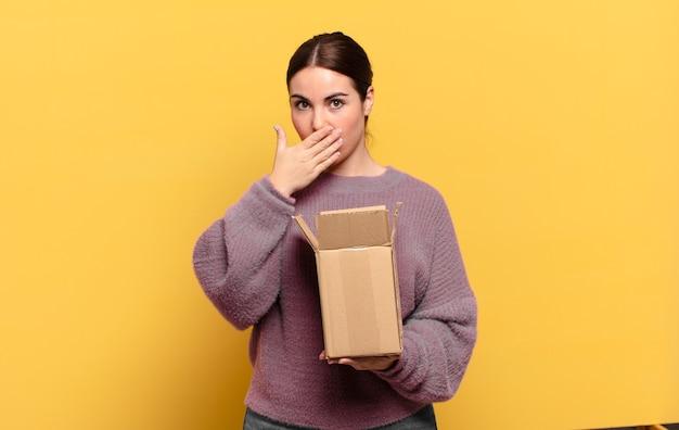 Giovane bella donna che copre la bocca con le mani con un'espressione scioccata e sorpresa, mantenendo un segreto o dicendo oops