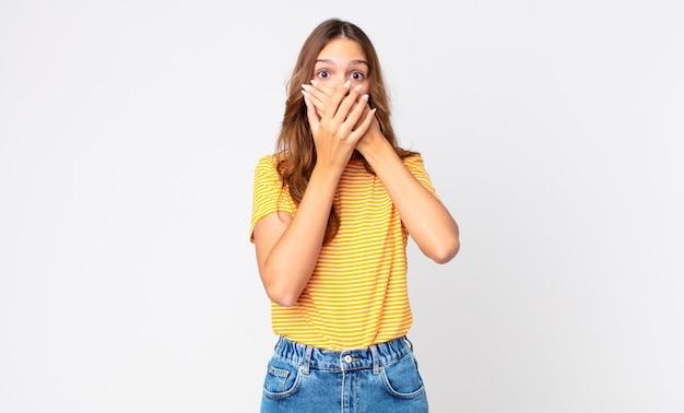 Giovane bella donna che copre la bocca con le mani con uno shock