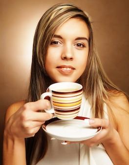 Giovane bella donna che beve caffè su sfondo beige