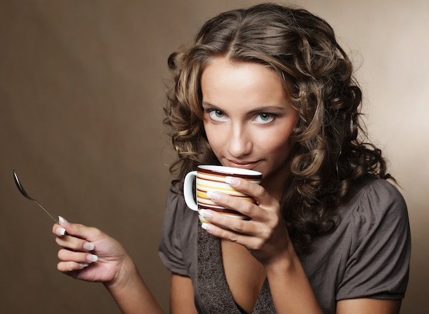 Giovane donna graziosa che beve caffè