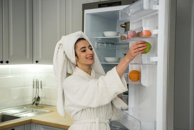 Giovane donna graziosa che mangia frutta in cucina, concetto di dieta. cibo sano per tutti
