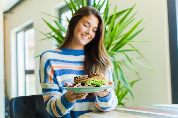 Giovane donna graziosa che mangia un panino a casa