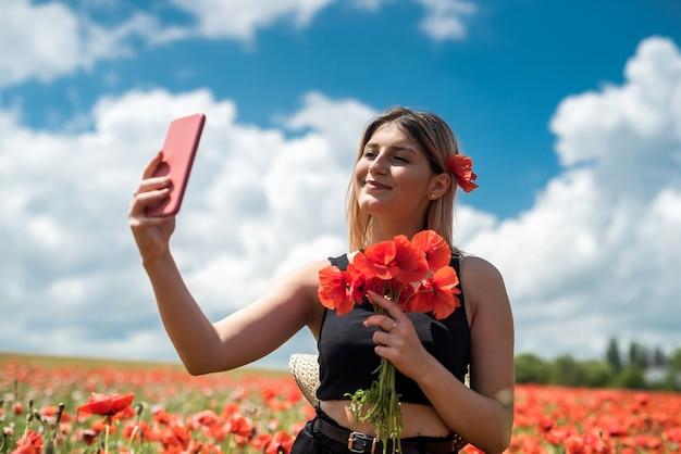 Giovane donna graziosa che gode dell'ora legale nel campo dei fiori di papaveri. la libertà