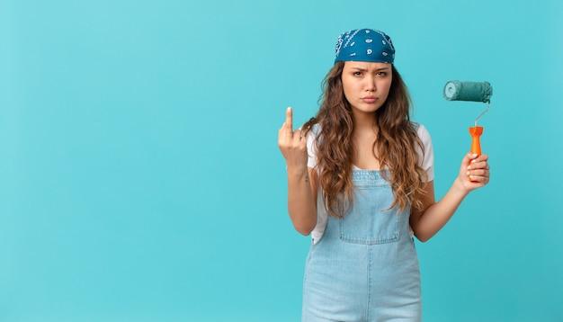 Giovane bella donna che si sente arrabbiata, infastidita, ribelle e aggressiva e dipinge un muro