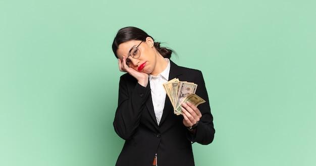 Giovane bella donna che si sente annoiata, frustrata e assonnata dopo un compito noioso, noioso e noioso, tenendo il viso con la mano. concetto di affari e banconote