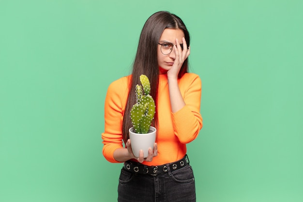 Giovane bella donna che si sente annoiata, frustrata e assonnata dopo un compito noioso, noioso e noioso, tenendo il viso con la mano. concetto di cactus