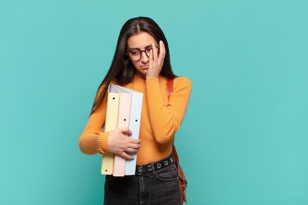 Giovane donna graziosa che si sente annoiata, frustrata e assonnata dopo un compito noioso, noioso e noioso, tenendo il viso con la mano. concetto di studente
