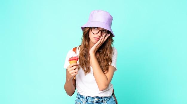 Giovane bella donna che si sente annoiata, frustrata e assonnata dopo una noiosa presa in mano di un gelato. concetto di estate