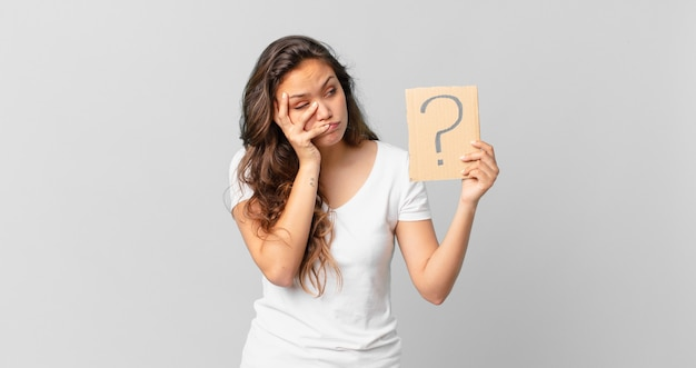 Giovane bella donna che si sente annoiata, frustrata e assonnata dopo un fastidioso e con in mano un segno di punto interrogativo