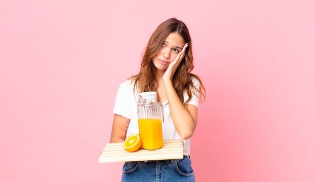 Giovane bella donna che si sente annoiata, frustrata e assonnata dopo una noiosa e con in mano un vassoio con un succo d'arancia