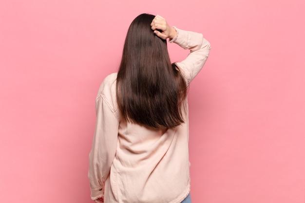 Giovane donna graziosa che si sente incapace e confusa, pensando a una soluzione, con una mano sull'anca e l'altra sulla testa, vista posteriore