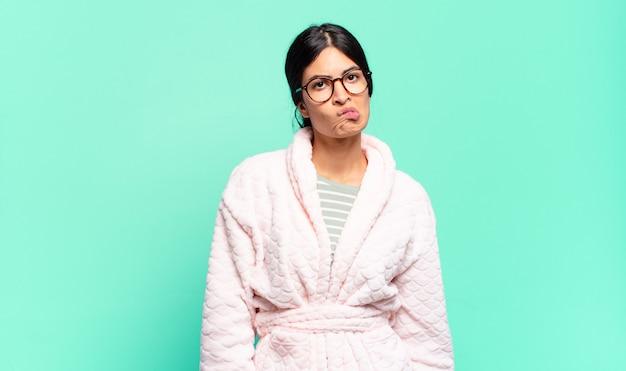 Giovane bella donna che si sente incapace, confusa e incerta su quale opzione scegliere, cercando di risolvere il problema. concetto di pigiama