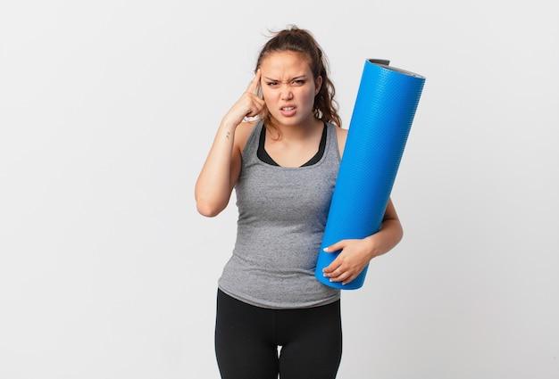 Giovane bella donna che si sente confusa e perplessa, mostra che sei pazzo e tiene in mano un tappetino da yoga