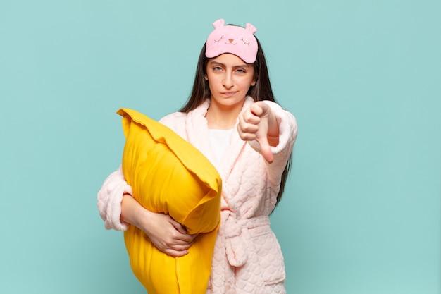Giovane donna graziosa che si sente arrabbiata, arrabbiata, infastidita, delusa o scontenta, mostrando i pollici verso il basso con uno sguardo serio. svegliarsi indossando il concetto di pigiama