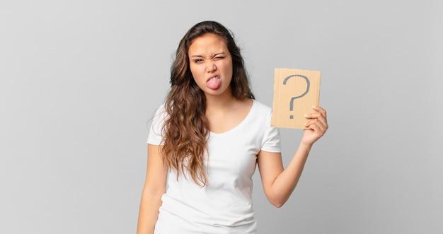 Giovane bella donna che si sente disgustata e irritata e con la lingua fuori e con in mano un segno di punto interrogativo