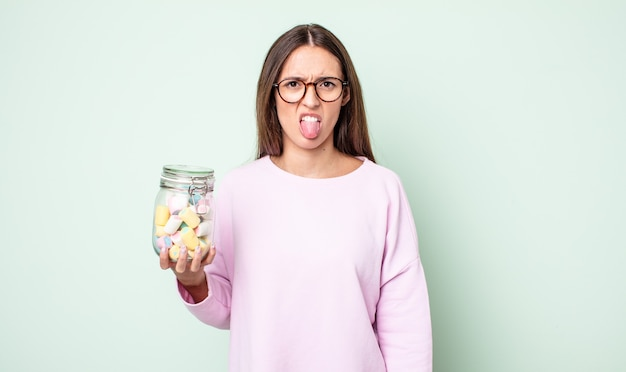 Giovane bella donna che si sente disgustata e irritata e con la lingua fuori. concetto di caramelle di gelatina