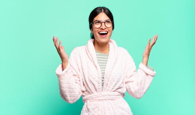 Giovane donna graziosa che si sente felice, stupita, fortunata e sorpresa, celebrando la vittoria con entrambe le mani in aria. concetto di pigiama