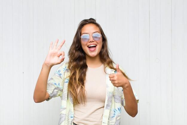 Giovane donna graziosa che si sente felice, stupita, soddisfatta e sorpresa, mostrando i gesti ok e il pollice in alto, sorridente