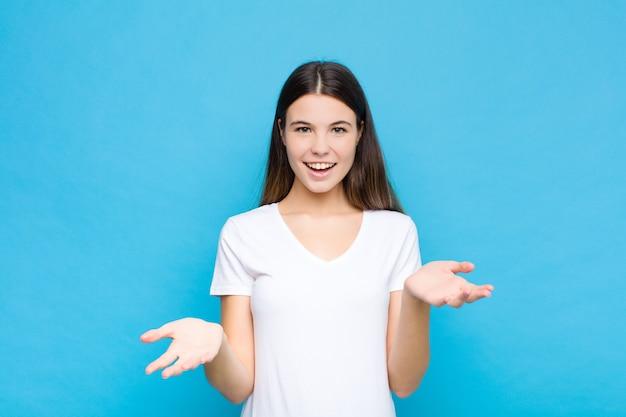 Giovane bella donna che si sente felice, stupita, fortunata e sorpresa, come dire sul serio omg? incredibile contro il muro blu